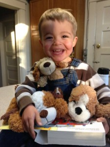Ben with stuffed dogs, smiling 11-15
